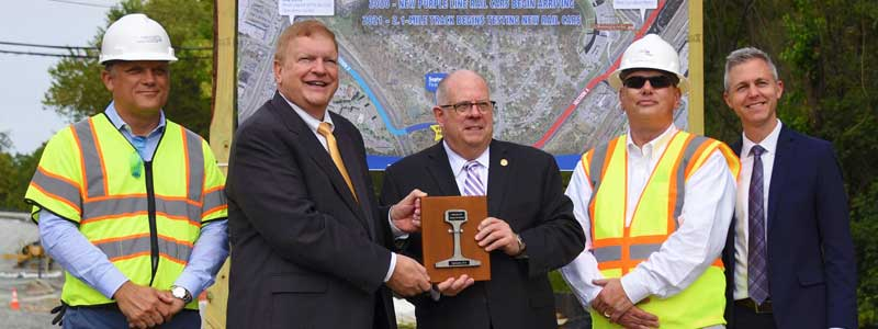 Governor Hogan with Transportation staff holding a piece of track